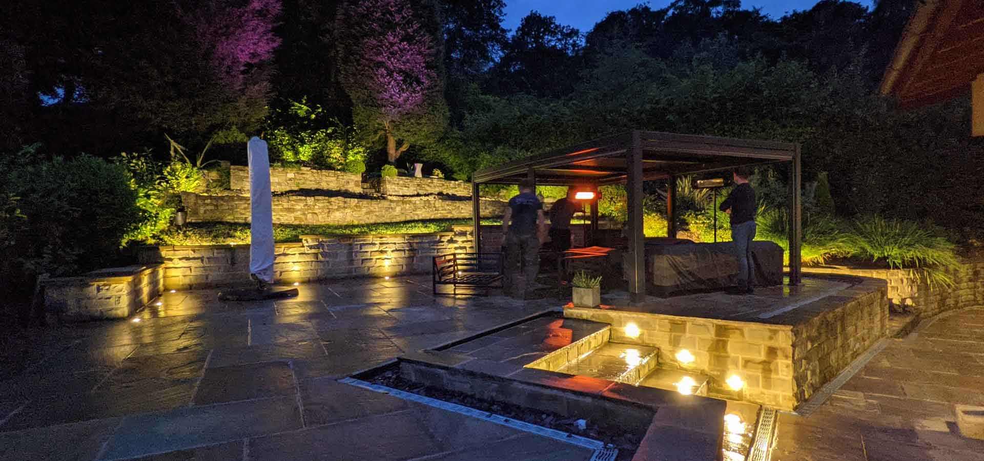A beautiful back garden in darkness with many areas illuminated with outdoor lighting