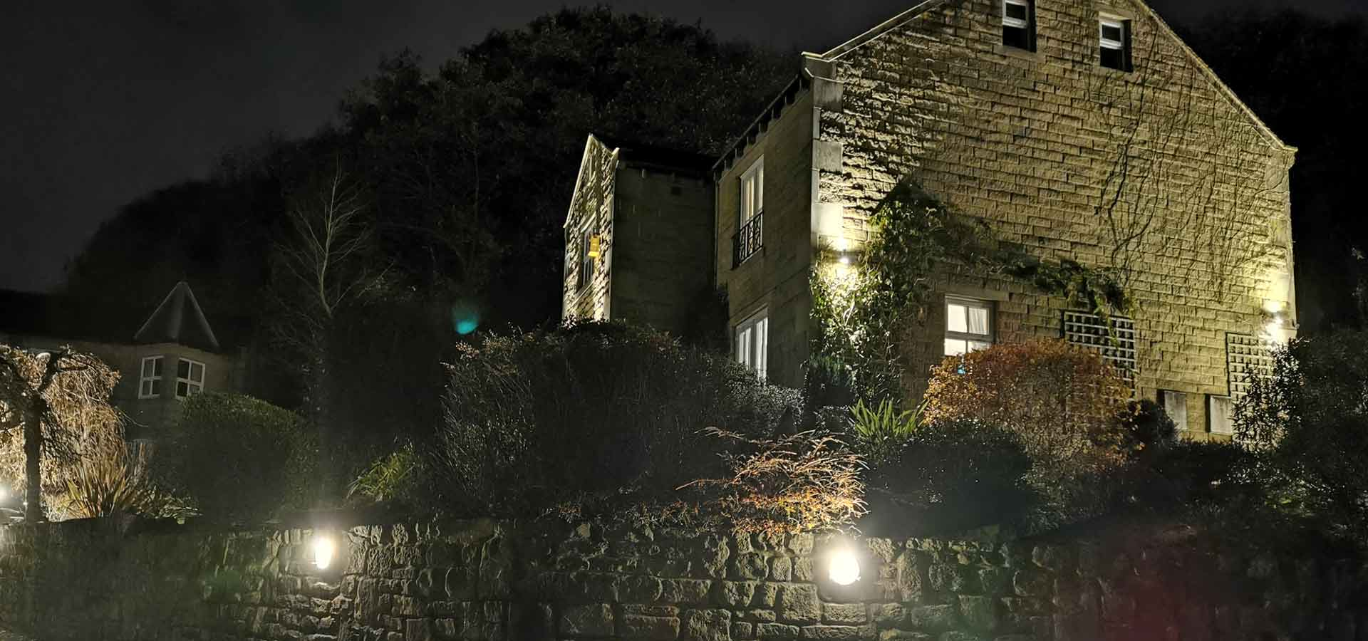 A large stone cottage from a side view in darkness lit up with outdoor lighting