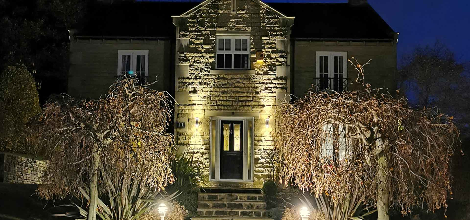 A large stone cottage in darkness lit up with outdoor lighting