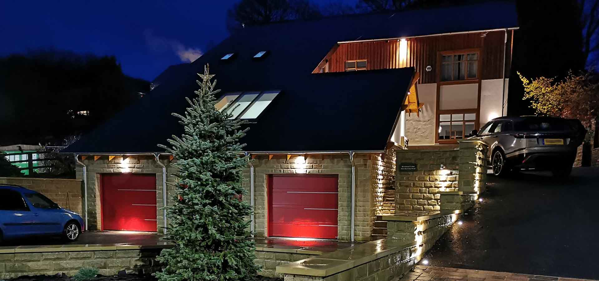 A large house with a double garage lit with outdoor lighting
